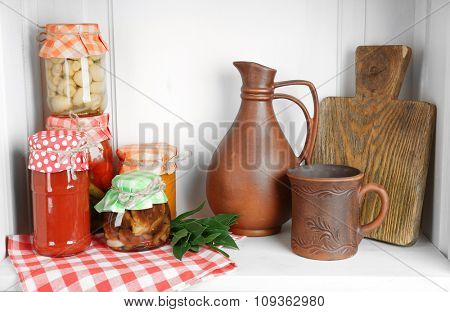 Jars with pickled vegetables and beans, spices, book of recipes and kitchen utensils on shelf