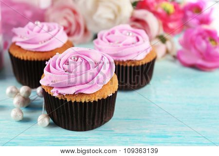 Tasty cupcakes and cup of tea on light background
