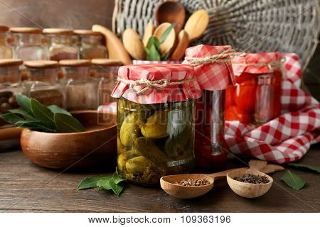 Jars with pickled vegetables and beans, spices, book of recipes and kitchen utensils on wooden background