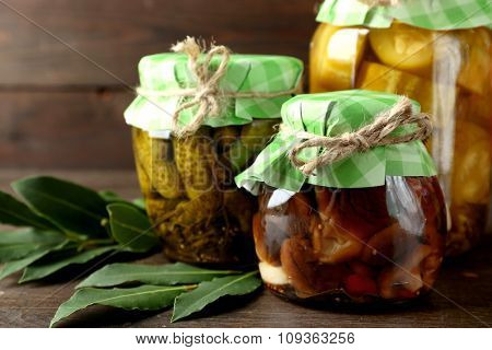Jars with pickled vegetables and mushrooms on wooden background