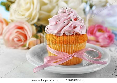 Tasty cupcake on plate, on light background