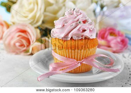 Tasty cupcake on plate, on light background