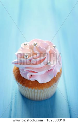 Tasty cupcake on color wooden background
