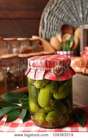 Jars with pickled cucumbers, spices and kitchenware on wooden background