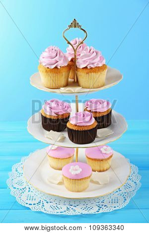 Tasty cupcakes on stand, on color background