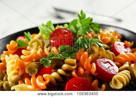 Delicious macaroni dish in black bowl on served grey wooden table, close up