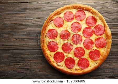 Tasty pizza with salami on wooden background