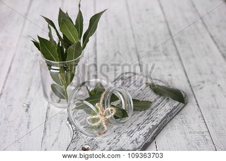 Fresh bay leaves in glass jar, on white wooden table