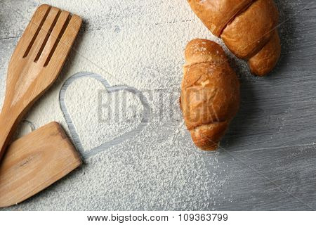 Heart of flour, croissant and  wooden kitchen utensils on gray background