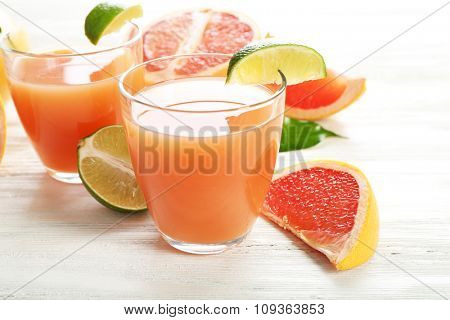 Two glasses of citrus juice and fresh fruits on light wooden background
