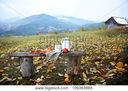 Old wooden bench with teapot, fruits and nuts on mountains background