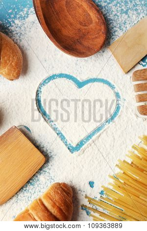 Heart of flour, foodstuffs and kitchen utensils on color wooden background