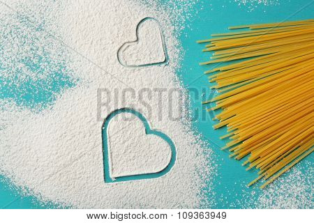 Heart of flour and pasta on blue background