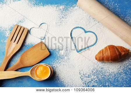 Heart of flour and  wooden kitchen utensils on blue background