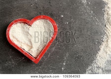 Heart of flour on gray background