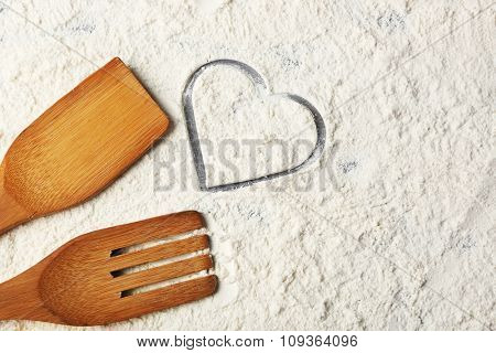 Heart of flour and  wooden kitchen utensils n on gray background