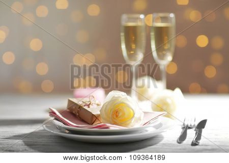 Glasses of wine and white roses, on blurred background