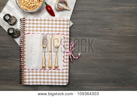Decorated cookbook on wooden background