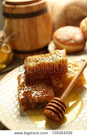 Honeycombs on plate on wooden background