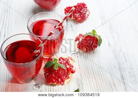 Two glasses of tasty juice and garnet fruit, on wooden background