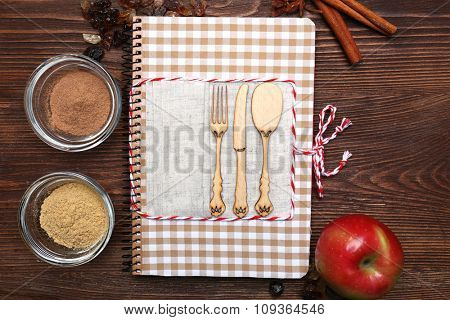 Decorated recipe book with ingredients on wooden background