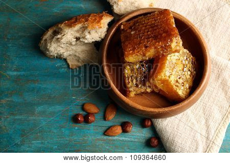 Honeycombs on plate on color wooden background