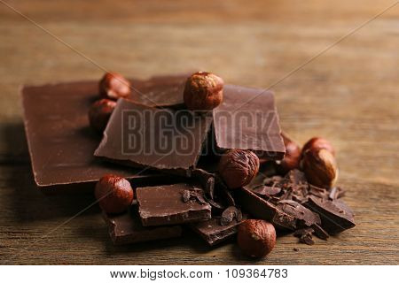 Black chocolate pieces with nuts on wooden background