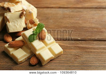 White chocolate pieces with nuts on color wooden background