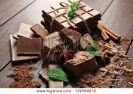 Variety of chocolate pieces, coffee grains and cocoa powder on wooden background