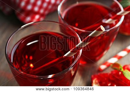 Two glasses of tasty juice and garnet fruit, on the table, close-up