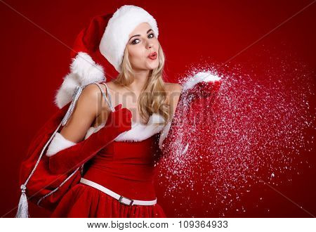 view of cute blond Santa girl blowing snowflakes from hand isolated on red background, celebration of Christmas time holidays