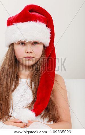Sad Little Girl Kid In Santa Claus Hat. Christmas.