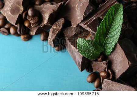 Black chocolate pieces and coffee grains on color wooden background