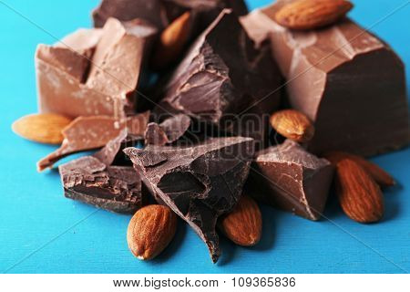Black chocolate pieces with nuts on color wooden background