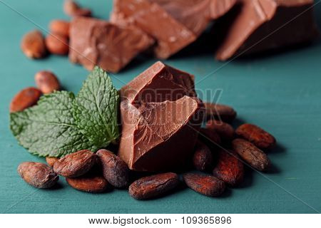 Milk chocolate pieces and cocoa beans on color wooden background