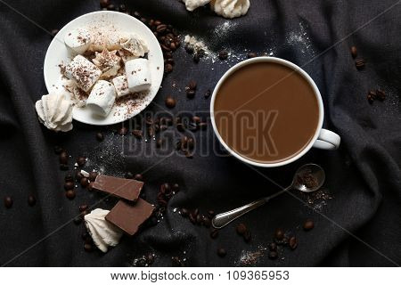 Cup of coffee with sweets on a black tablecloth