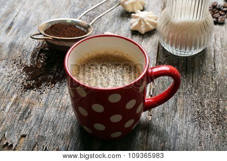 Cup of coffee with sweets on wooden background