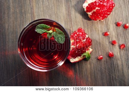 A glass of tasty juice and garnet fruit, on wooden background, top view