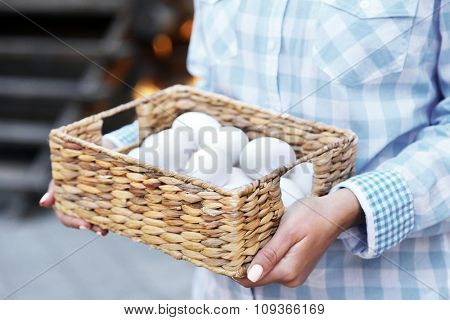 Eggs in basket in women hands outdoors