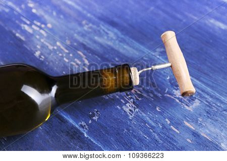 Corkscrew and wine bottle on blue wooden background