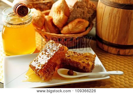 Honeycombs on plate, hot buns in basket on wooden background