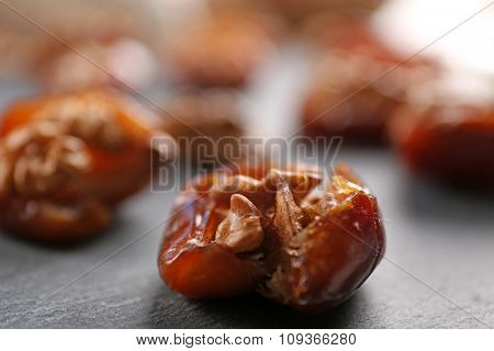 Walnut and date fruit on wooden table, close-up