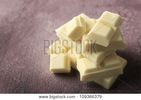 White chocolate pieces on color wooden background