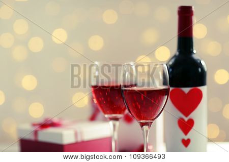 Setting of glasses with wine, bottle and a gift in the box, on white blurred background