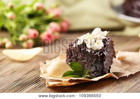 Piece of chocolate cake decorated with flowers on brown wooden table