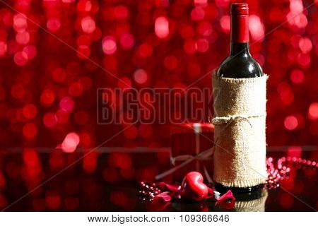 Setting of a bottle of wine, a gift in the box and other decoration, on red blurred background