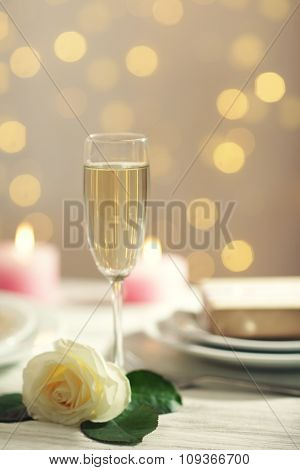 A glass of wine, a white rose and a gift in the box, on blurred background