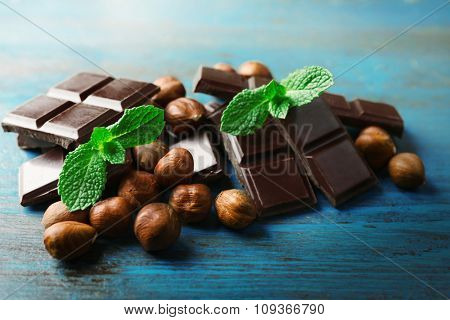 Chocolate pieces with nuts on color wooden background