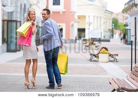 Young couple with shopping bags outdoors