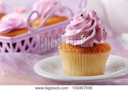 Tasty cupcake on saucer, on light background